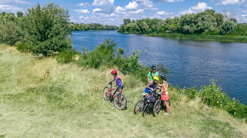 Family on bikes cycling outdoors, active parents and kids on bicycles, aerial view of happy family with children relaxing. Near beautiful river from above stock images