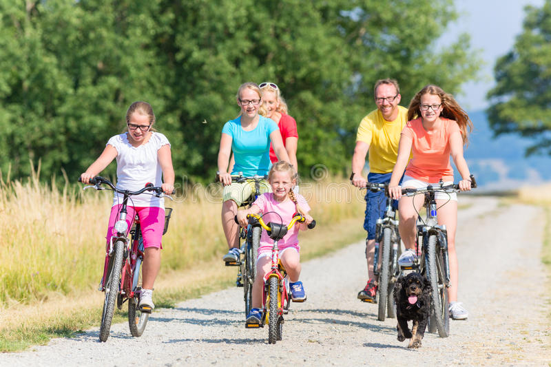 Family on bikes at dirt path. Family on bikes riding down dirt path, mother, father and children together stock photo