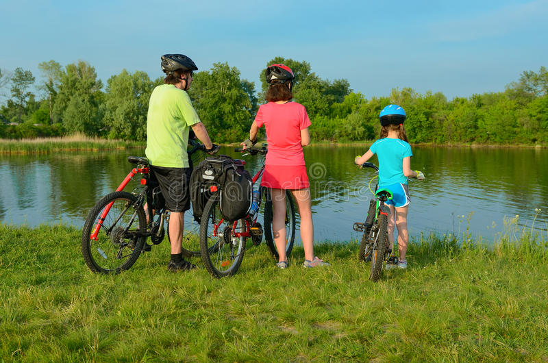 Family on bikes outdoors, active parents and kid cycling and relaxing near beautiful river, fitness royalty free stock image