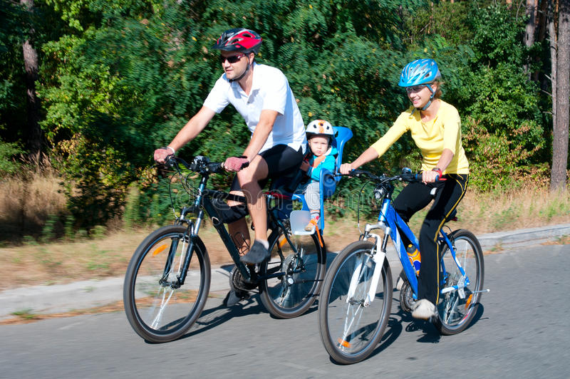 Family on the bikes in the sunny stock photo