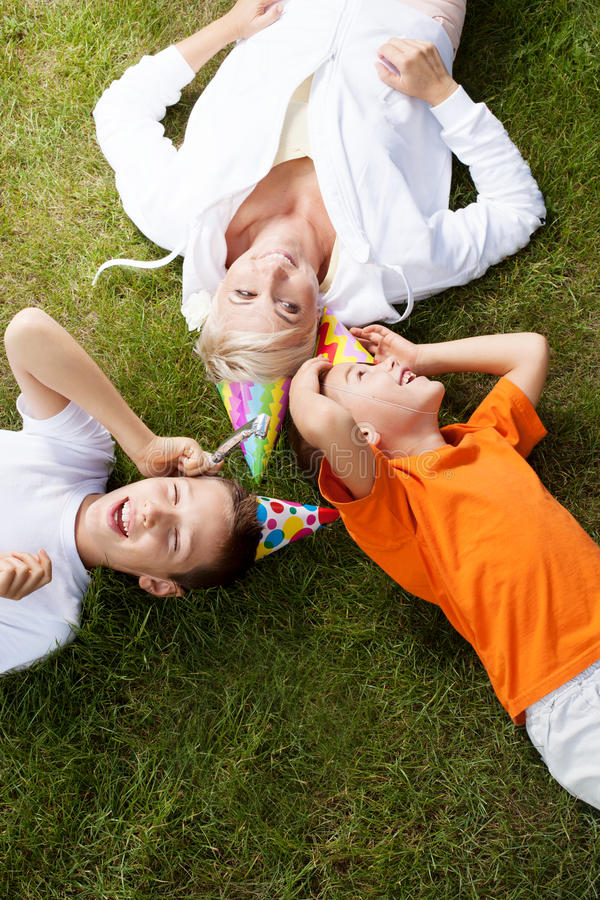 Family birthday party. Happy mother with her sons, birthday party in garden. Outdoor photo royalty free stock photography