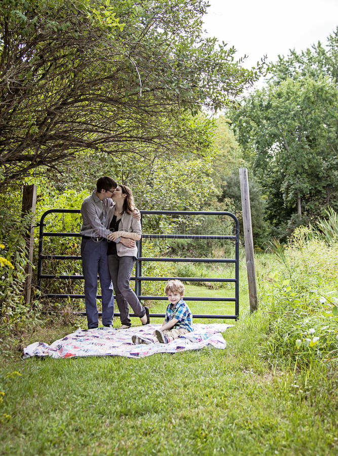 Family on blanket in the country. Kissing parents with a boy sitting on a blanket outside royalty free stock photo