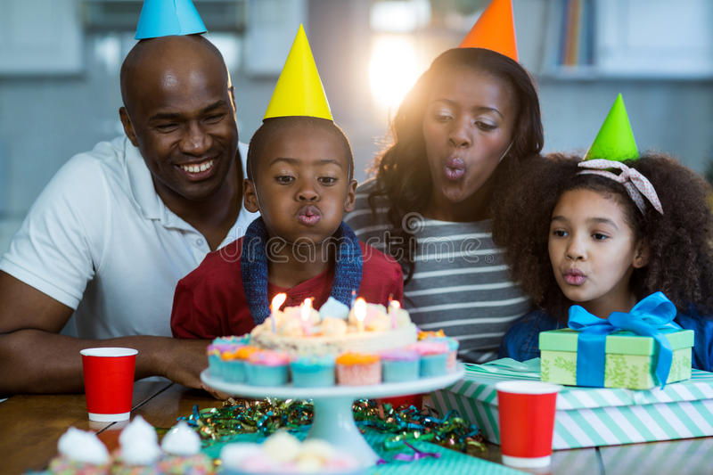 Family blowing out candles on birthday cake. At home stock images