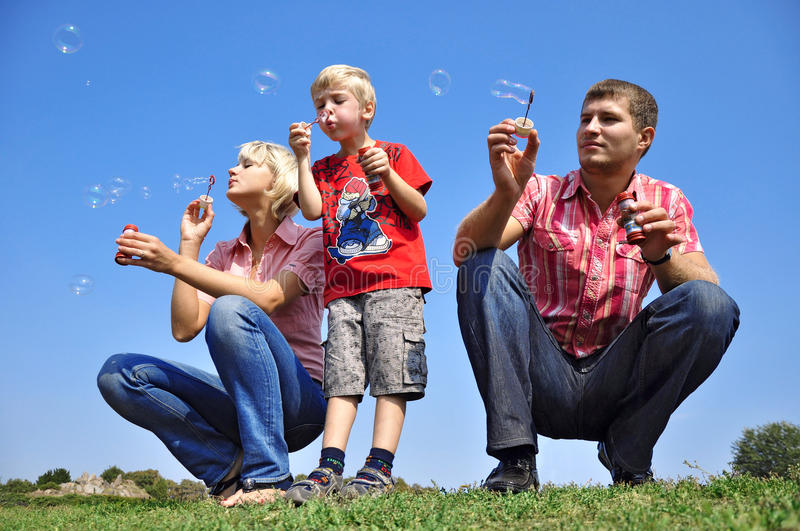 Family blowing soap bubbles. Happy family blowing soap bubbles royalty free stock images