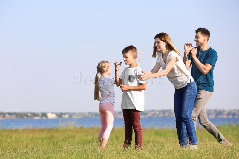 Family blowing soap bubbles near river on summer day royalty free stock image