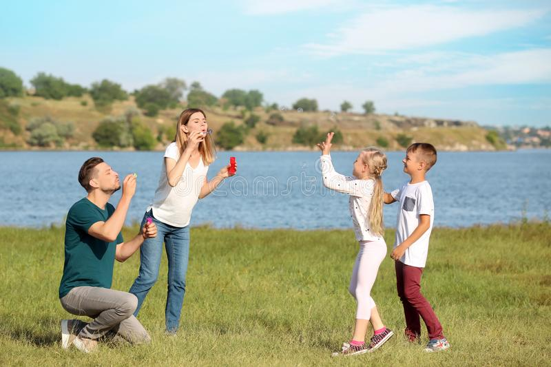 Family blowing soap bubbles near river on summer day royalty free stock photography