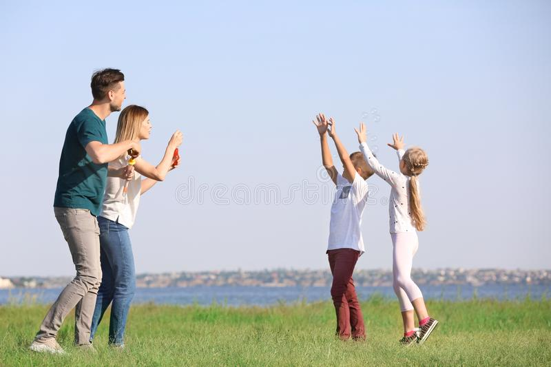 Family blowing soap bubbles near river on summer day stock photos