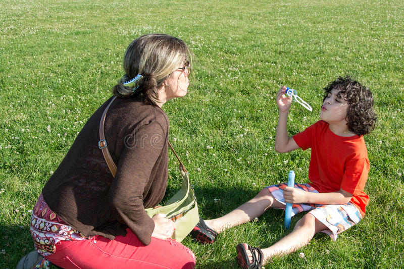 Family blowing soap bubbles in a park during summer. Single mother and her son having fun in a park during summer. Boy blowing soap bubbles. Happy family royalty free stock image