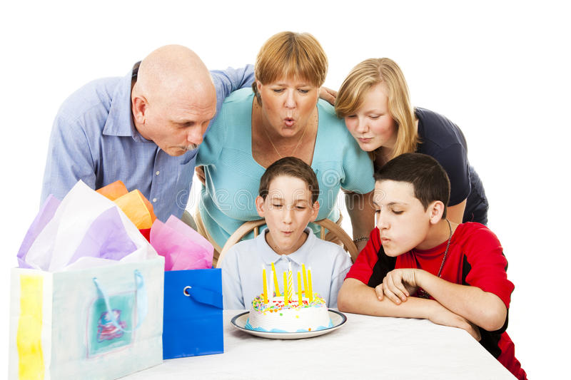 Family Blows Out Birthday Candles stock image