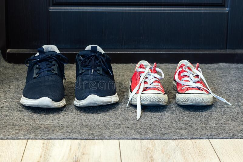 Family blue shoes and red sneakers on the rug at the front door. Closeup view royalty free stock image