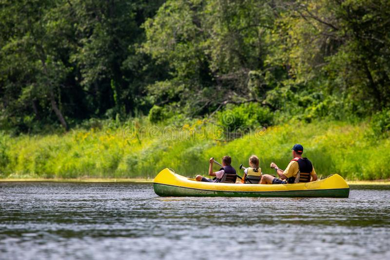 Family in boat trip by boat on the river. Family in yellow kayak drives on the river. People boating on river Gauja in Latvia, peacefull nature scene. By boat royalty free stock photo