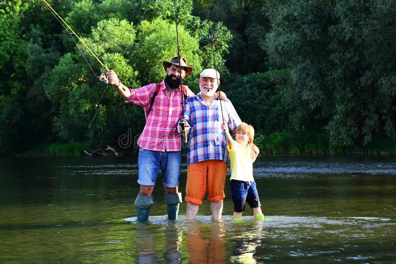 Family bonding. Father, son and grandfather fishing. Men day. Male multi generation family. Father, son and grandfather stock image