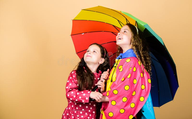 Family bonds. Little girls in raincoat. autumn fashion. cheerful hipster children, sisterhood. rain protection. Rainbow. Happy little girls with colorful stock photo