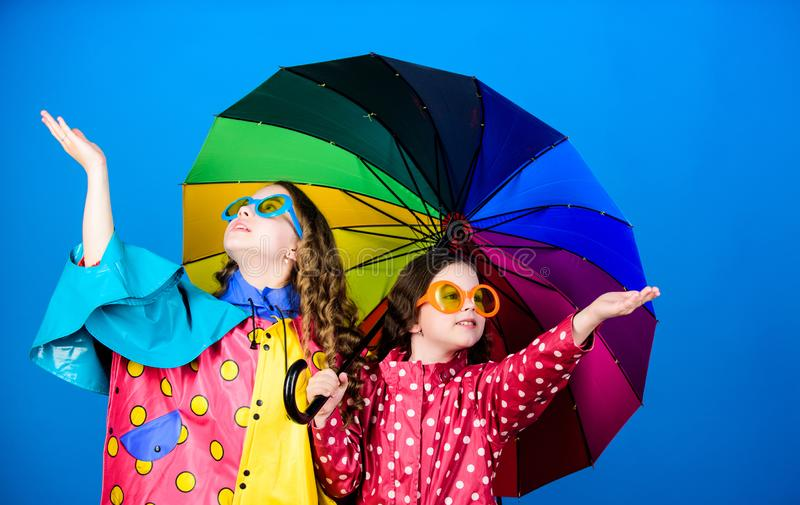 Family bonds. Small girls in raincoat. happy small girls with colorful umbrella. rain protection. Rainbow. autumn. Fashion. cheerful hipster children royalty free stock photo