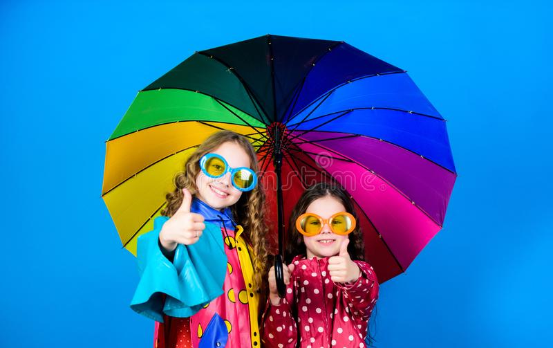 Family bonds. Small girls in raincoat. rain protection. Rainbow. autumn fashion. cheerful hipster children, sisterhood. Happy small girls with colorful royalty free stock photo