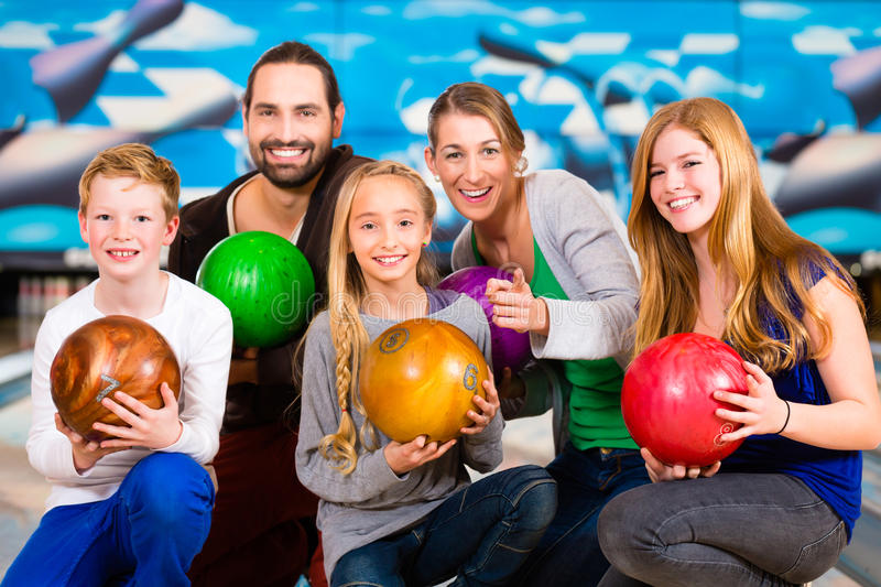 Family at Bowling Center. Parents playing with children together at bowling center royalty free stock photography