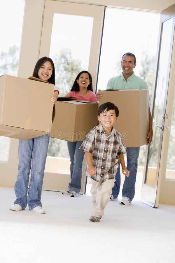 Family With Boxes Moving Into New Home Stock Photo