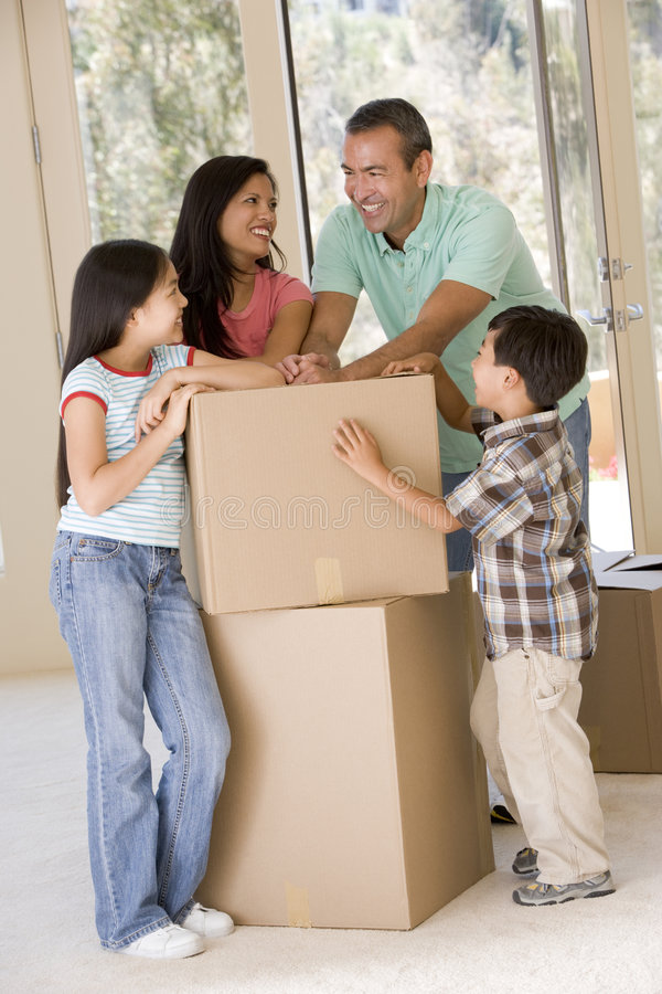 Family with boxes in new home smiling royalty free stock photo