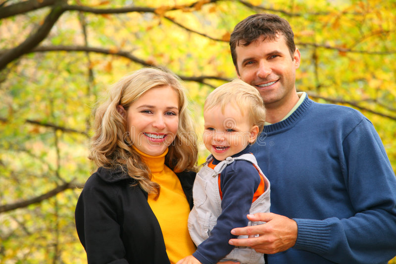 Family with boy in autumn park. Happy family with boy in autumn park royalty free stock photo