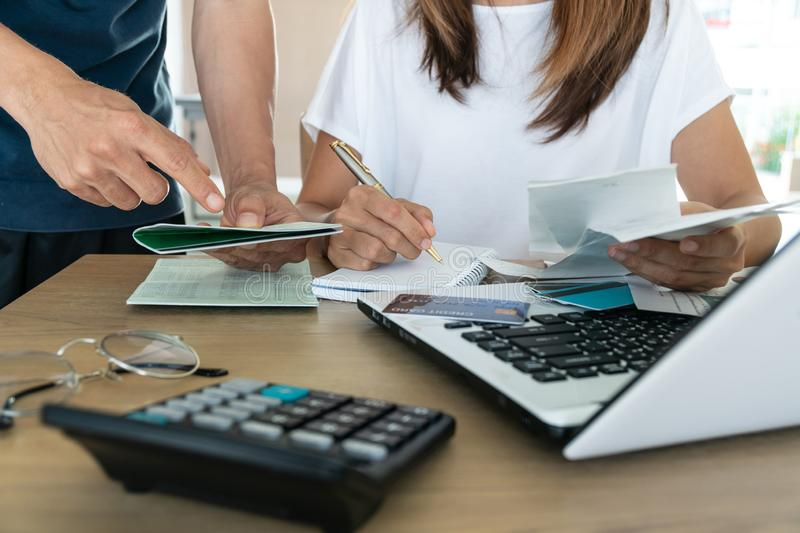 Family budget and finances. Young woman doing accounts together with her husband at home stock photography