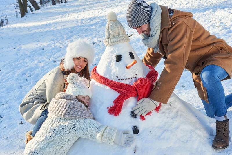 Family builds snowman in winter royalty free stock photo