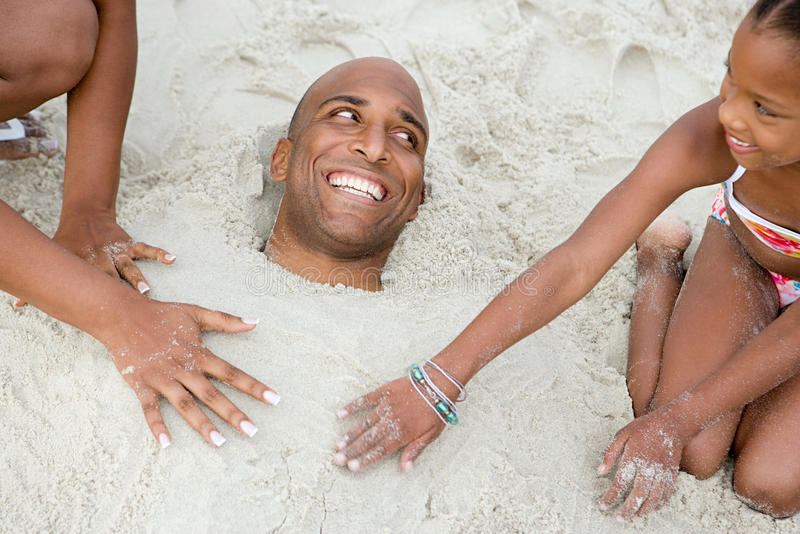 Family burying father in sand stock image