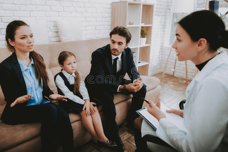 Family in Bussiness Clothers with Psychologist. Family in Bussiness Clothers. Happy Family. Psychologist in White Coat. Psychologist`s Office. Write stock photo