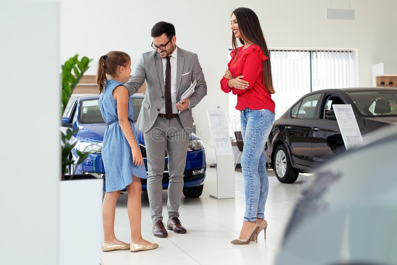Family buying a new car in the car dealership saloon stock image