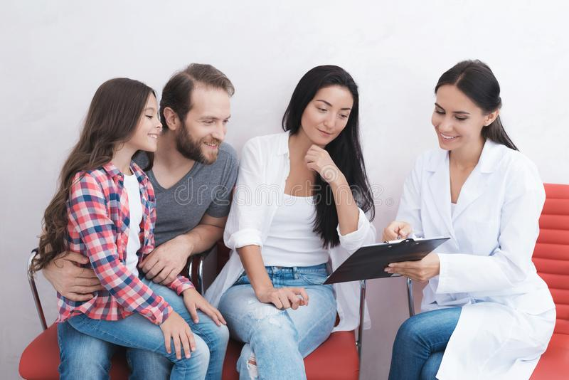 The family came to see a dentist in a medical clinic. The secretary helps fill in all the necessary papers. The girl sits on her lap beside the man stock photography