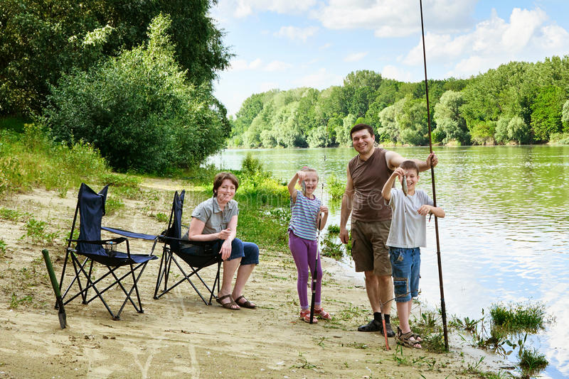 Family camping and fishing, people active in nature, child caugh. T fish on bait, river and forest, summer season royalty free stock photos