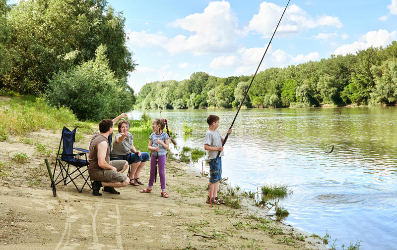 Family camping and fishing, people active in nature, child caugh. T fish on bait, river and forest, summer season royalty free stock image
