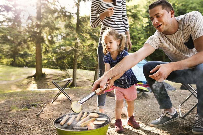 Family camping in forest, cooking meat on barbecue grill. Beautiful family enjoying camping holiday in forest. Father cooking meat on barbecue grill royalty free stock image