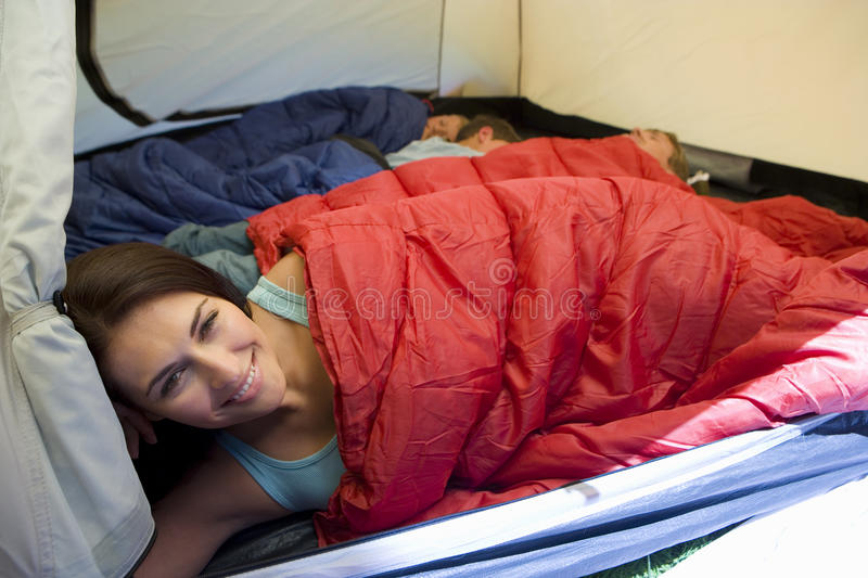 Family camping in tent, children (8-10) sleeping in background, focus on mother resting in sleeping bag in foreground, smiling, po royalty free stock images