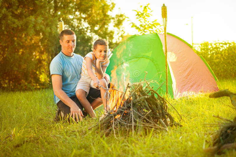 Family on a camping trip, the father and son baking sausage royalty free stock image