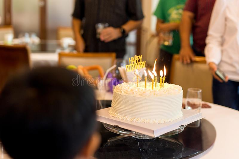 Family with a candle cake celebrates a birthday party in a restaurant. royalty free stock photos