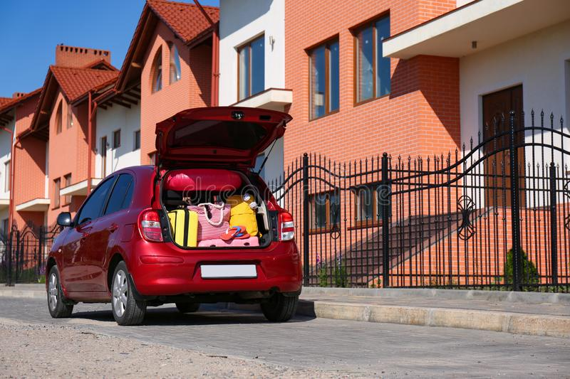 Family car with open trunk full of luggage in city. Space for text royalty free stock images