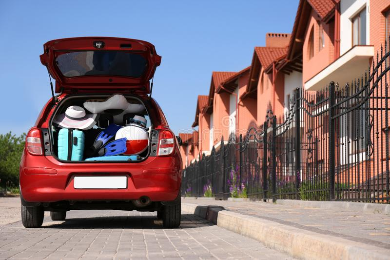 Family car with open trunk full of luggage in city. Space for text stock image