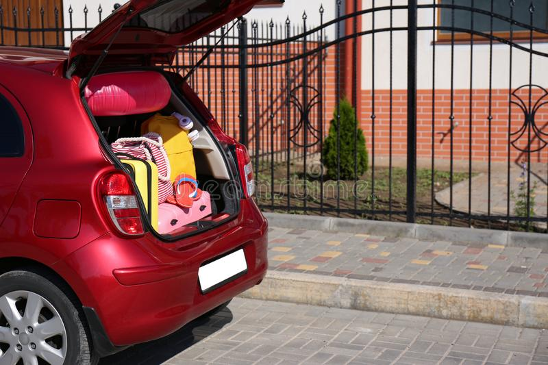 Family car with open trunk full of luggage in city. Space for. Text royalty free stock image