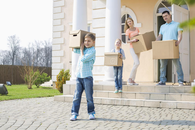 Family with cardboard boxes moving out from house royalty free stock images