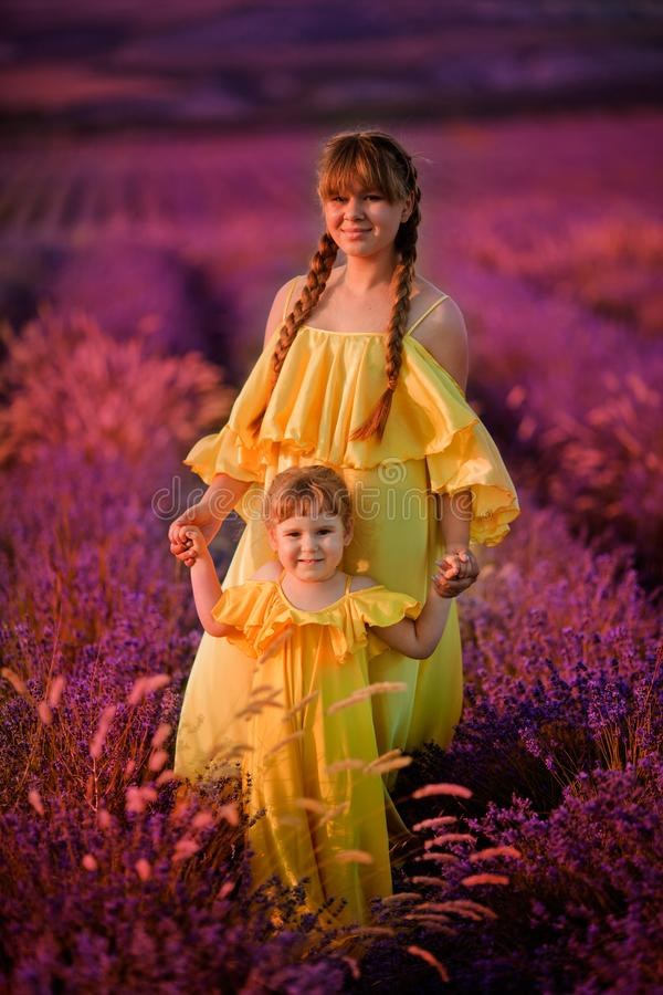 Family. care for the younger ones. sisters with a doll in their hands in a lavender field. Closing bright light royalty free stock photo