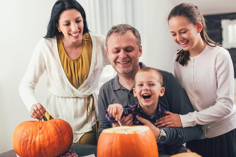 Family carving big orange pumpkin for Halloween royalty free stock images