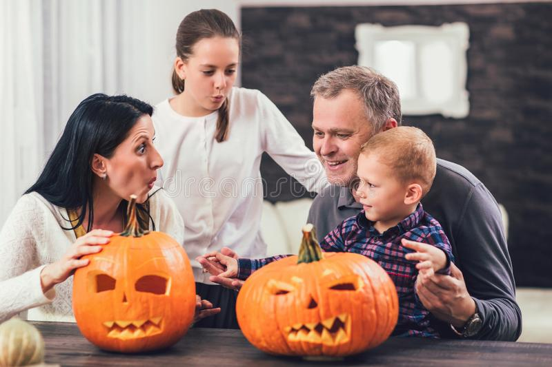 Family carving big orange pumpkin for Halloween stock photo