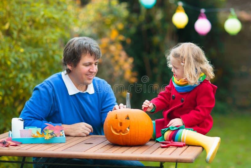 Family carving Halloween pumpkin stock photos