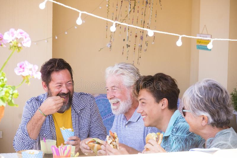 Family caucasian people with mixed generations and years age have fun together eating fast food hamburger like lunch at home - stock photos