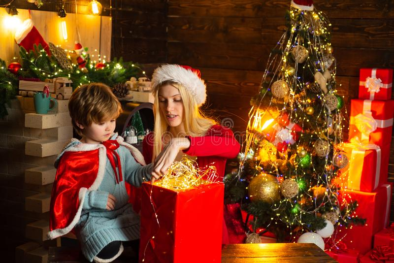 Family celebrate christmas. Mother with son and gift. Girl winter clothes santa claus hat celebrate christmas and happy stock photography