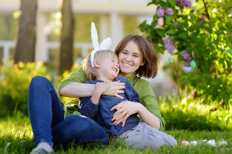 Family celebrate Easter holiday in spring park. Adorable little boy and his charming mother sitting on the grass, embracing and royalty free stock photos
