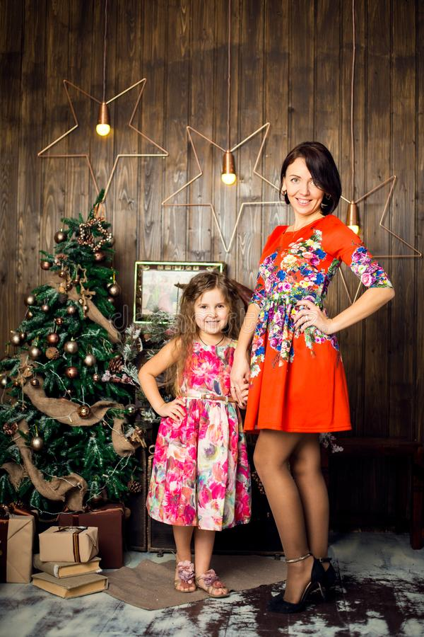 Family celebrates Christmas. Girl and mother near a decorated Christmas tree. Merry Christmas and happy holidays. Tenderness,. Caring and Understanding stock image