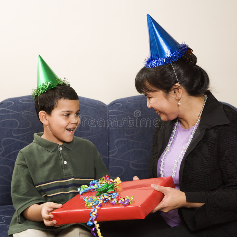 Family celebrating birthday. Mother giving present to surprised son at birthday party stock photography