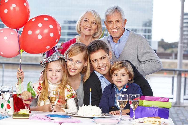 Family celebrating birthday. Happy family with children and grandparents celebrating birthday together for a girl royalty free stock images