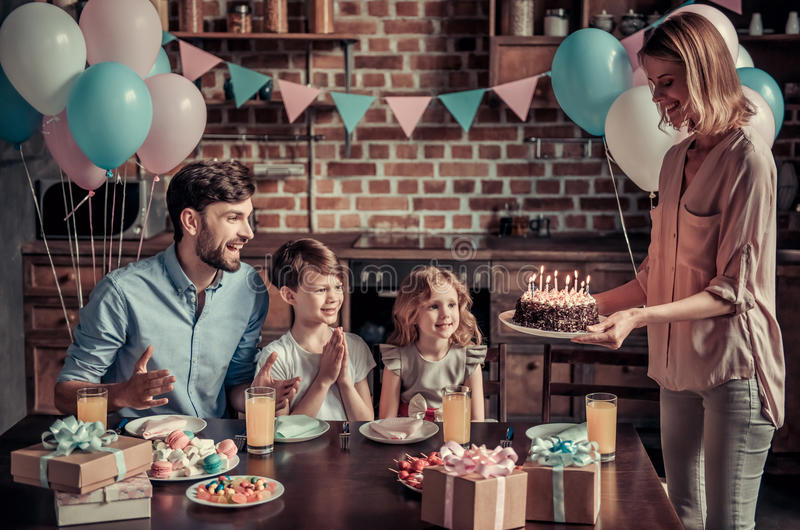 Family celebrating birthday. Happy family is sitting at the table in decorated kitchen during birthday celebration, mom is holding a birthday cake royalty free stock photography